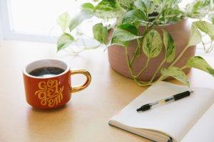 Notitieboek op tafel met pen en rode kop koffie